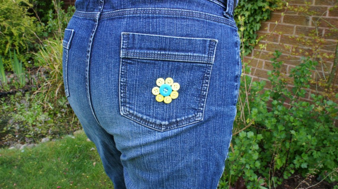 jeans rear pocket decorated with button flower yellow